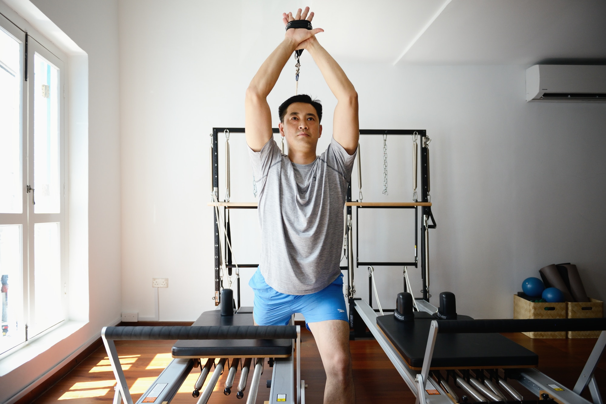 Image of a man doing Pilates with equipment - Pilates Products & Services