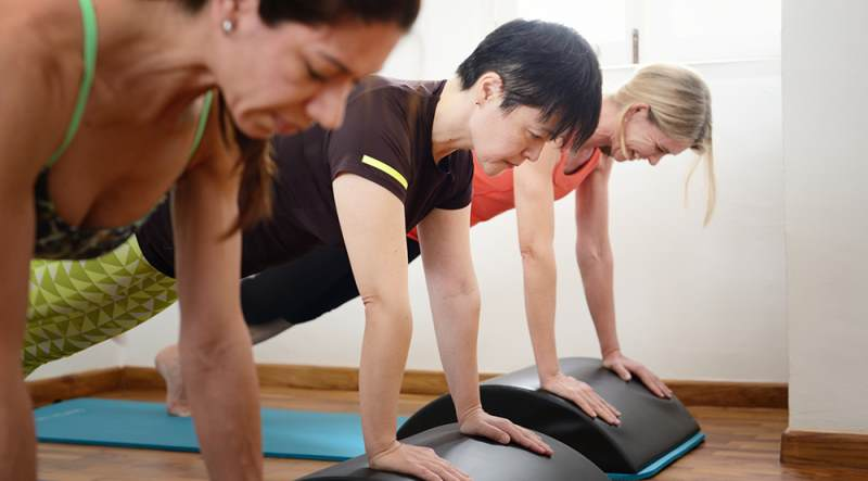 Image of three women learning pilates